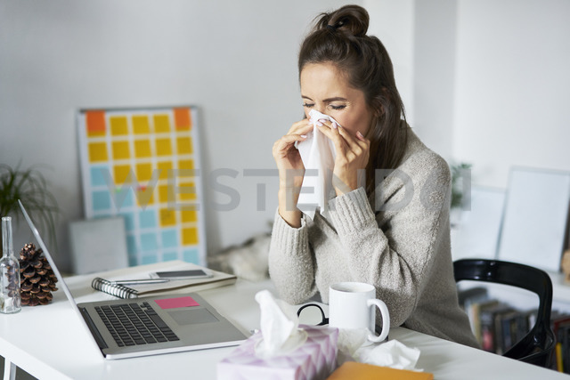 Ill woman at home at desk blowing her nose - BSZF00184