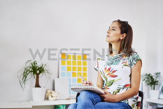 Thoughtful young woman sitting on chair taking notes - BSZF00196