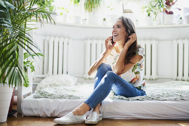 Happy young woman talking on the phone at home - BSZF00199