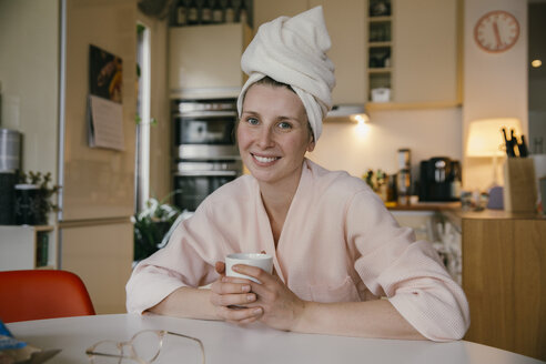 Portrait of smiling woman wearing a towel turban sitting with cup of coffee at table in the kitchen - MFF04373