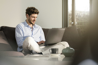 Man sitting on couch at home using laptop - SBOF01257