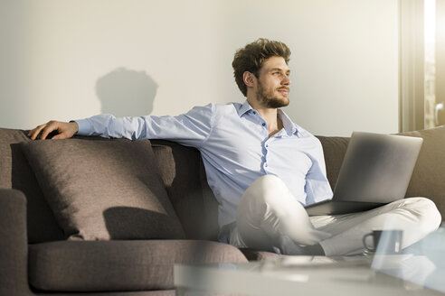 Man sitting on couch at home with laptop - SBOF01260