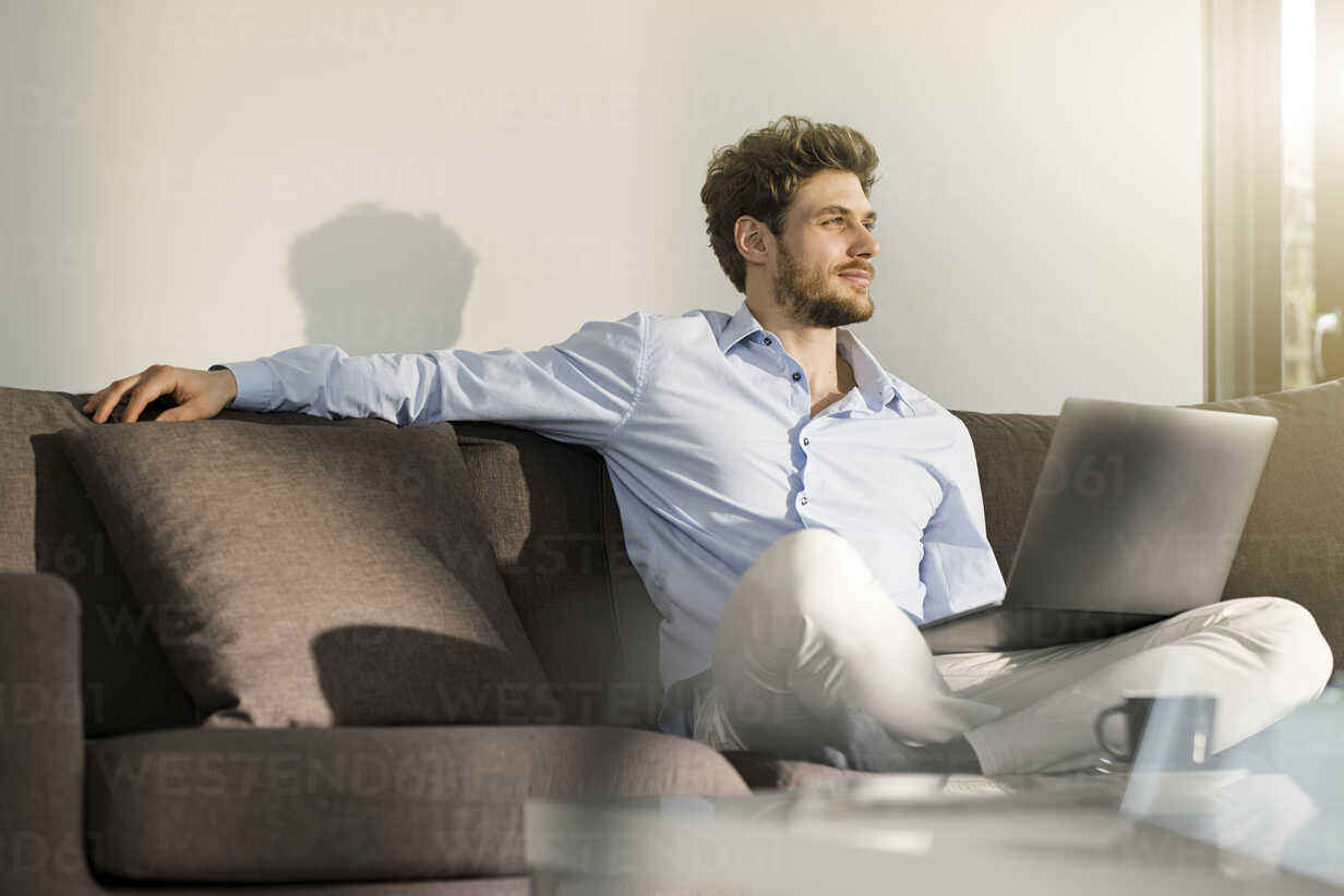 Man sitting on couch at home with laptop - SBOF01260 - Steve Brookland/Westend61