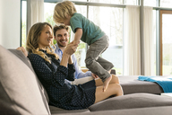 Happy parents playing with son on sofa at home - SBOF01266