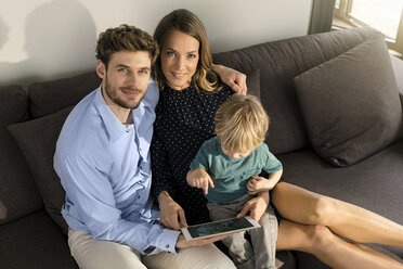 Portrait of smiling parents and son sitting on sofa with tablet at home - SBOF01272