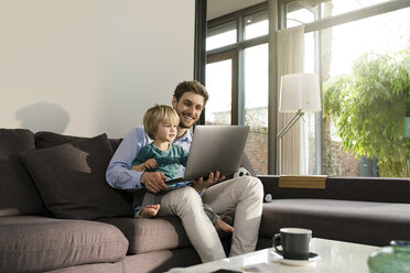 Father and son looking at laptop on couch at home - SBOF01275