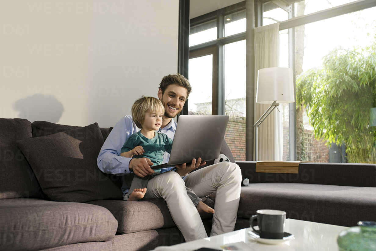 Father and son looking at laptop on couch at home - SBOF01275 - Steve Brookland/Westend61