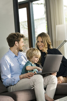 Smiling parents and son sitting on sofa with laptop at home - SBOF01278