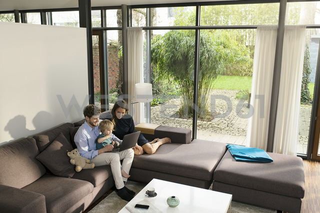 Parents and son sitting on sofa in modern living room using laptop at home - SBOF01281 - Steve Brookland/Westend61