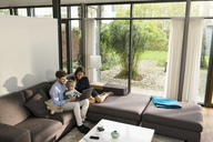 Parents and son sitting on sofa in modern living room using laptop at home - SBOF01281