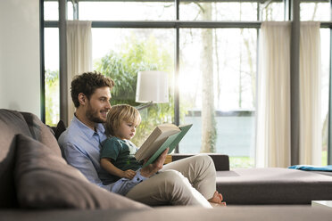 Father and son reading book on couch at home - SBOF01284