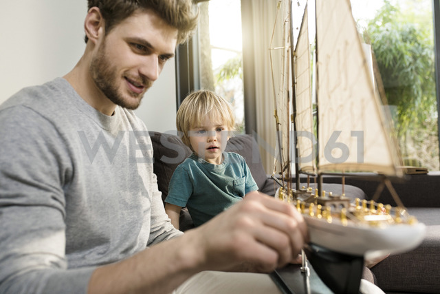 Father and son looking at toy model ship on couch at home - SBOF01287