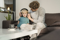 Father putting on headphones on son on couch at home - SBOF01290