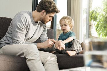 Son examining father's smartwatch on couch at home - SBOF01293