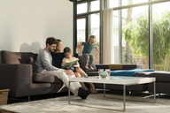 Family on sofa at home reading book with boy jumping - SBOF01299