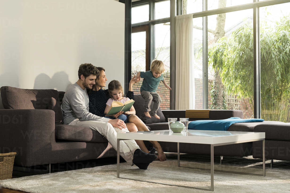 Family on sofa at home reading book with boy jumping - SBOF01299 - Steve Brookland/Westend61