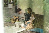 Happy parents and daughter playing guitar on sofa at home - SBOF01302