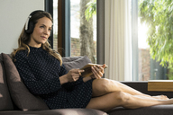 Woman with tablet and headphones relaxing on couch at home - SBOF01305