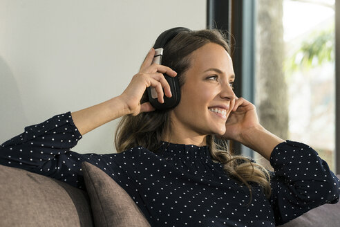 Smiling woman with headphones relaxing on couch at home - SBOF01308