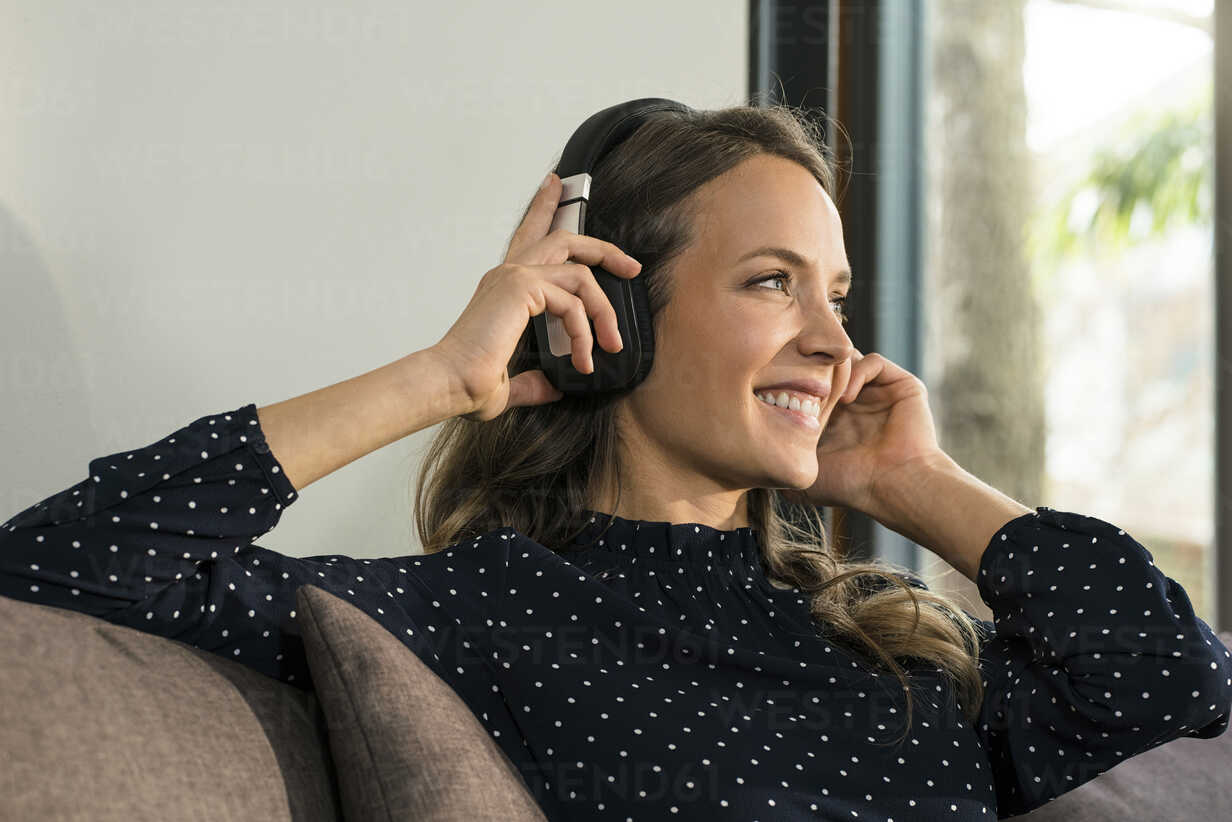 Smiling woman with headphones relaxing on couch at home - SBOF01308 - Steve Brookland/Westend61