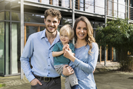 Portrait of smiling parents with son in front of their home - SBOF01311