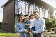 Portrait of smiling family in front of their home - SBOF01323