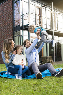 Happy family on blanket in garden in front of their home with father litfting up son - SBOF01326