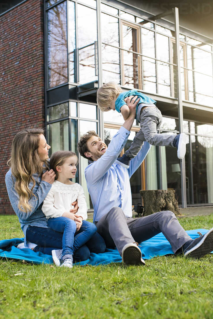 Happy family on blanket in garden in front of their home with father litfting up son - SBOF01326 - Steve Brookland/Westend61