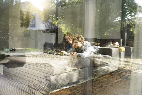 Smiling couple using laptop lying on sofa at home - SBOF01329