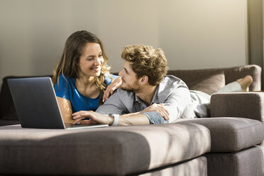 Smiling couple with laptop lying on sofa at home - SBOF01332
