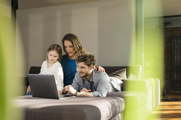 Family using laptop on sofa at home - SBOF01335