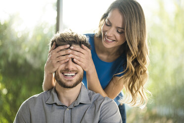 Smiling woman covering her boyfriend's eyes - SBOF01338