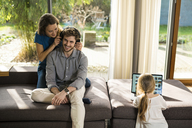 Couple with heaphones and daughter with laptop on sofa at home - SBOF01341