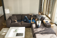 Couple with tablet and smartphone relaxing on sofa in modern living room at home - SBOF01344