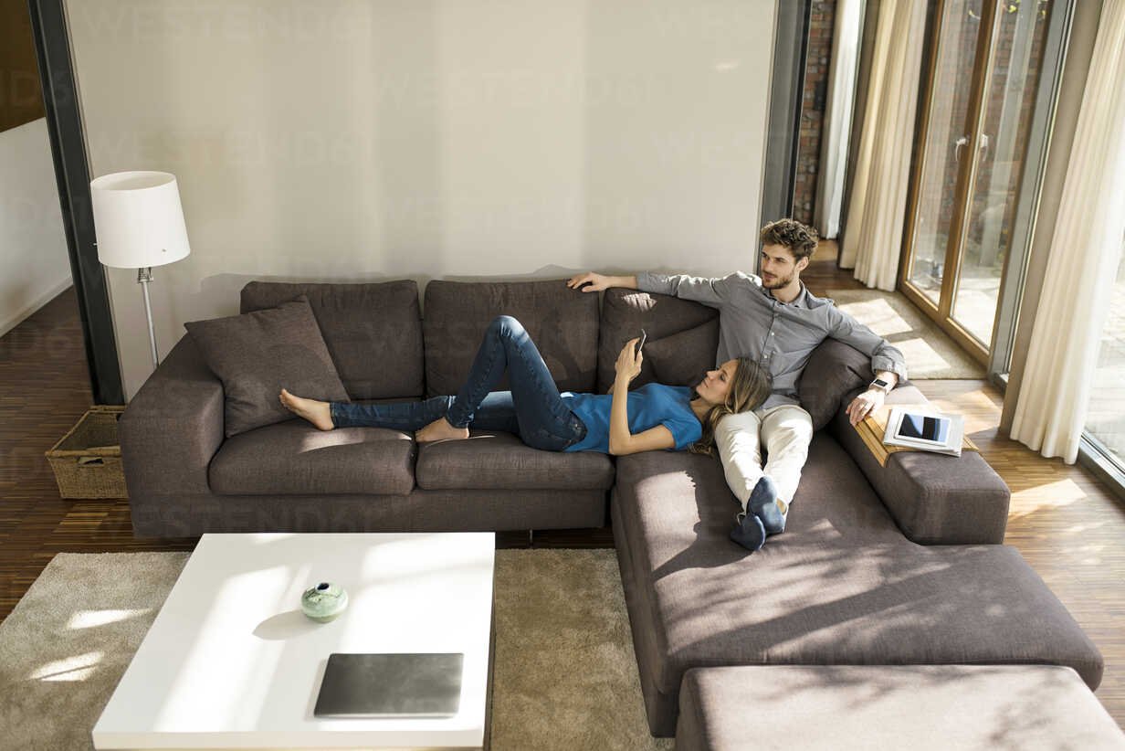 Couple with tablet and smartphone relaxing on sofa in modern living room at home - SBOF01344 - Steve Brookland/Westend61