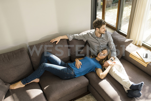 Affectionate couple relaxing on sofa at home - SBOF01347 - Steve Brookland/Westend61