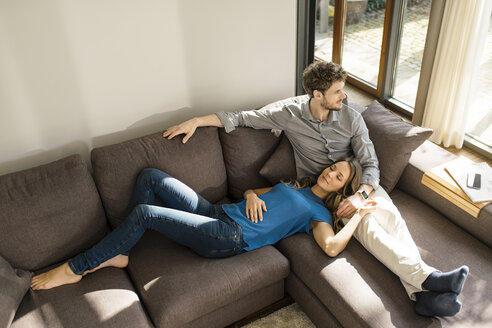 Affectionate couple relaxing on sofa at home - SBOF01347