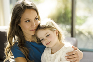 Portrait of smiling mother holding her daughter  in front of window - SBOF01350