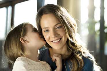 Smiling girl whispering into her mother's ear - SBOF01353