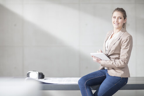 Portrait of smiling young woman with blueprint, VR glasses and tablet in office - ZEF14907