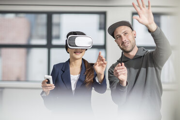 Man instructiong businesswoman wearing VR glasses in office - ZEF14913