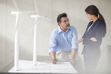 Colleagues with wind turbine models in office discussing plan - ZEF14919
