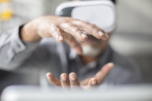 Man shaping with his hands wearing VR glasses in office - ZEF14925