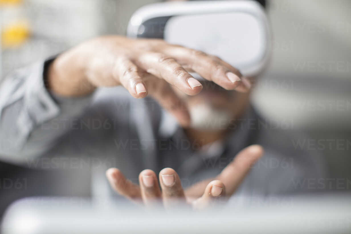 Man shaping with his hands wearing VR glasses in office - ZEF14925 - zerocreatives/Westend61