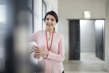 Portrait of smiling young woman standing on the corridor in office - ZEF14931