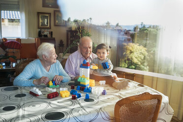 Great-grandparents and baby girl playing together with plastic building bricks at home - GEMF01858