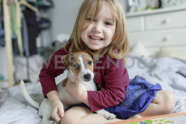Portrait of happy little girl crouching on bed with Jack Russel Terrier puppy - KMKF00142