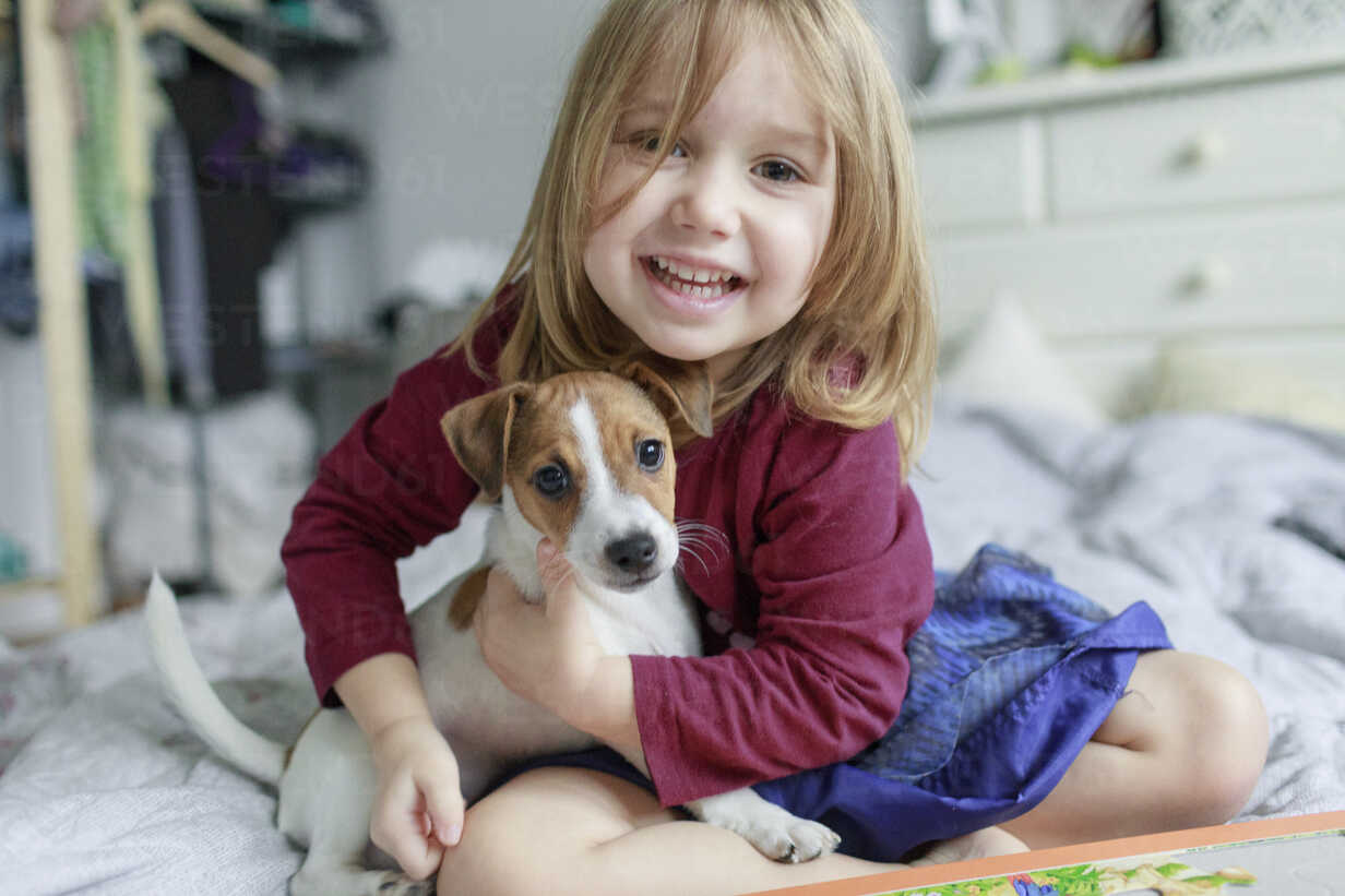 Portrait of happy little girl crouching on bed with Jack Russel Terrier puppy - KMKF00142 - Katharina Mikhrin/Westend61