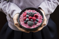 Girl holding bowl with overnight oats mit frozen berries - LVF06642