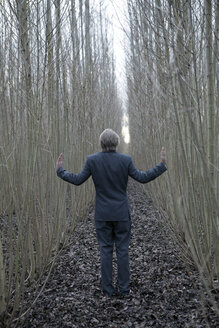 Businessman standing amidst willows - PSTF00065